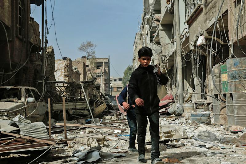 Children walk among the rubble after an airstrike in Douma, in the eastern Ghouta region of Syria, on Monday. The latest strikes killed at least 13 people overnight, the Syrian Observatory for Human Rights said. (HASAN MOHAMED/AFP via Getty Images)