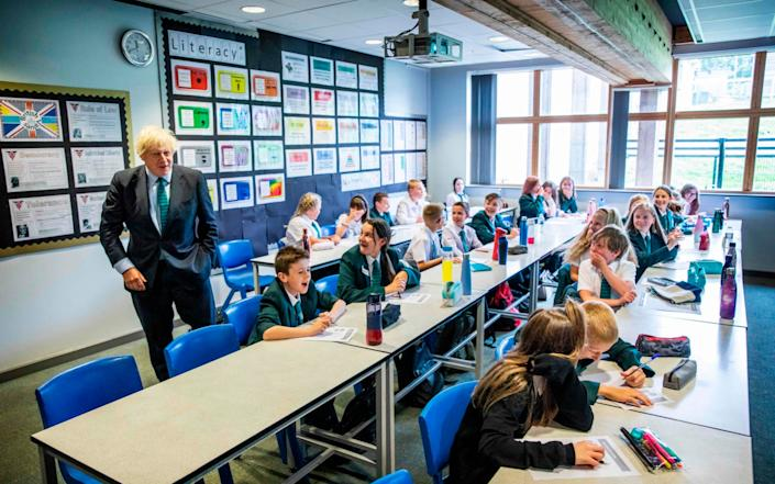 Boris Johnson talks to a class of year seven pupils on their first day at Castle Rock school, Coalville, central England - AFP