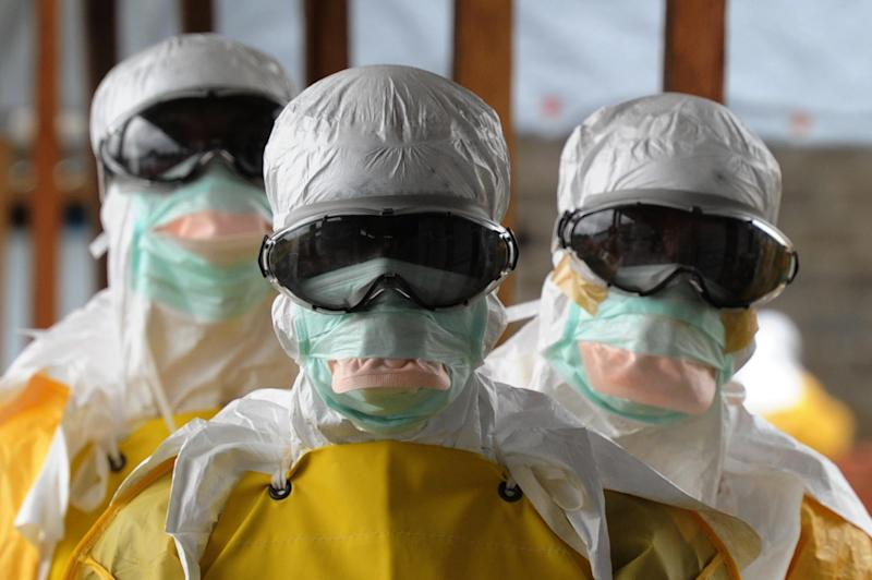 Health care workers, wearing protective suits, leave a high-risk area at the French NGO Medecins Sans Frontieres (Doctors without borders) Elwa hospital on August 30, 2014 in Monrovia, Liberia