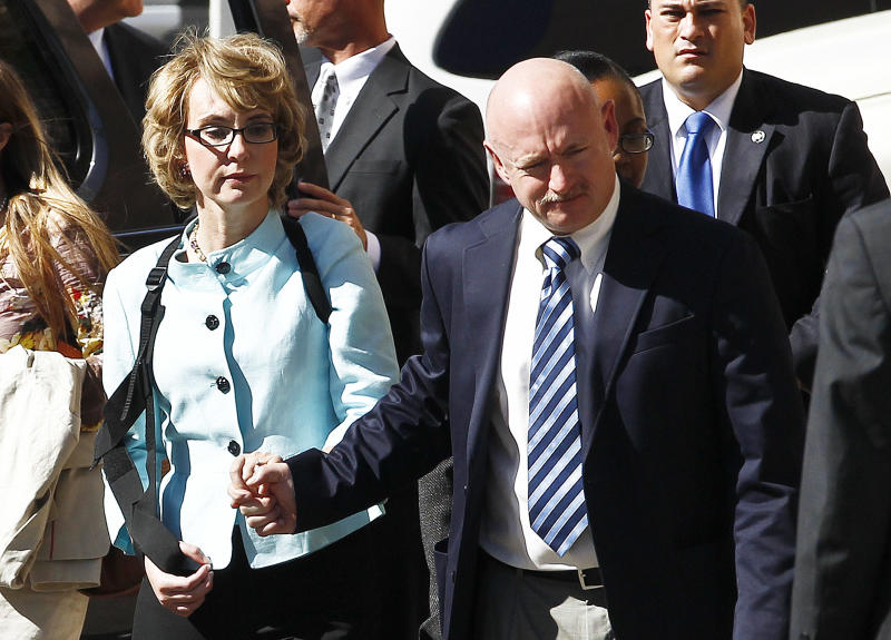 FILE - In a Thursday, Nov. 8, 2012 file photo, former Democratic Rep. Gabrielle Giffords, left, and her husband Mark Kelly holds her hand as they leave after the sentencing of Jared Loughner, in back of U.S. District Court, in Tucson, Ariz. Giffords and her husband launched a political action committee aimed at curbing gun violence on Tuesday, Jan. 8, 2013, as her Arizona hometown paused to mark the second anniversary of a deadly shooting rampage that left her with severe injuries.  (AP Photo/Ross D. Franklin, File)
