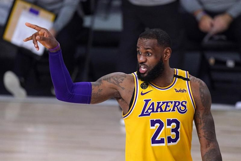 Los Angeles Lakers' LeBron James talks to his teammates during the second half of an NBA conference.