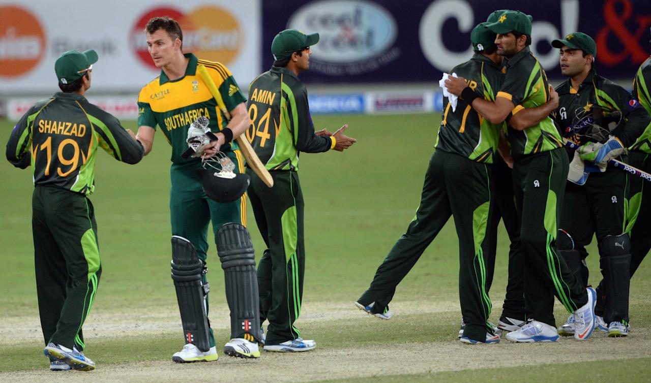 Pakistani cricketer Ahmed Shahzad (L) shakes hands with South African cricketer Ryan McLaren (2nd L) after wining the second day-night international against South Africa in Dubai Cricket Stadium in Dubai on November 1, 2013. Pakistan won the second day-night international against South Africa by 66 runs in Dubai on Friday, to level the five-match series at 1-1. AFP PHOTO/ ASIF HASSAN        (Photo credit should read ASIF HASSAN/AFP/Getty Images)