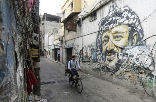 Mohammed rides his bicycle past a mural painting of the late Palestinian leader Yasser Arafat south of the Lebanese capital Beirut on May 29, 2018