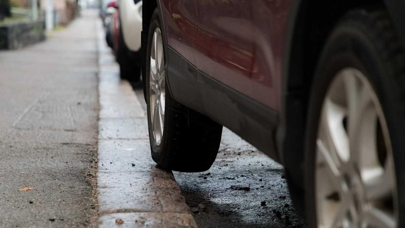 Bad car parking with rear tyre on pavement