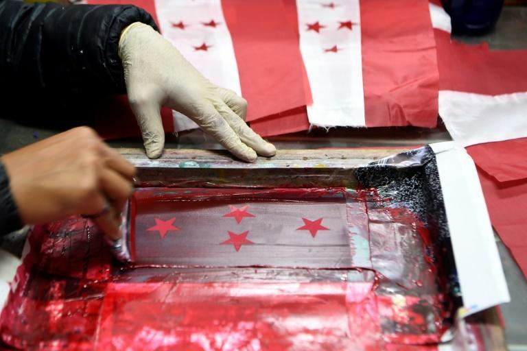 A worker prints Nepali Congress party flags at a printing workshop in Kathmandu
