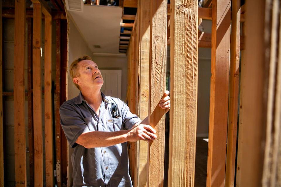 A man holds a 2-by-4 stud that is part of the framing of a building project