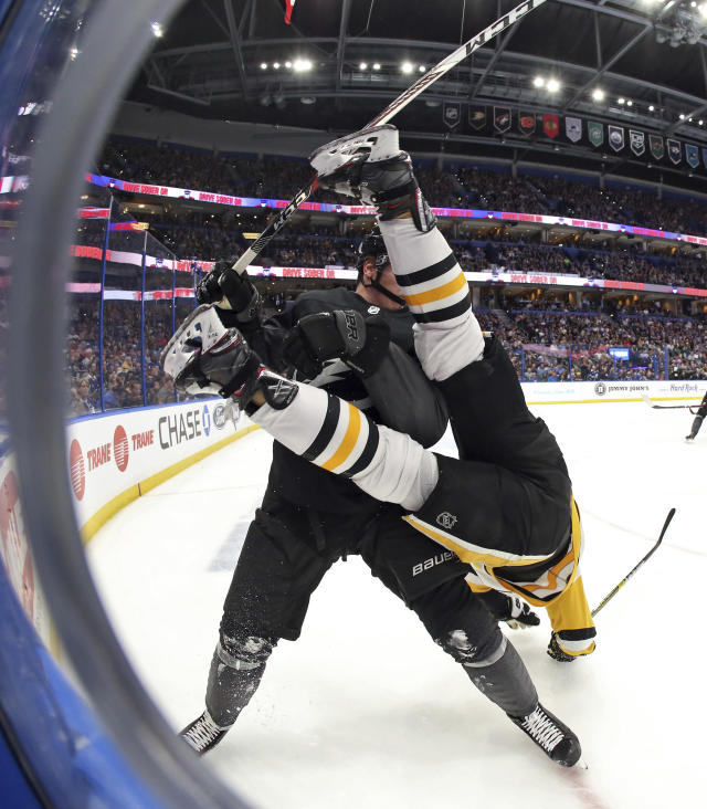 Tampa Bay Lightning defenseman Mikhail Sergachev, left, upends Pittsburgh Penguins left wing Tanner Pearson during the third period of an NHL hockey game Saturday, Feb. 9, 2019, in Tampa, Fla. (AP Photo/Chris O'Meara)