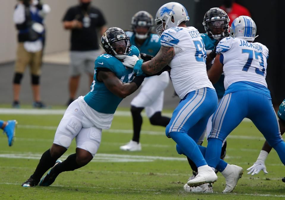Detroit Lions tackle Taylor Decker holds the line against Jacksonville Jaguars linebacker K'Lavon Chaisson during the first quarter at TIAA Bank Field, Oct. 18, 2020.