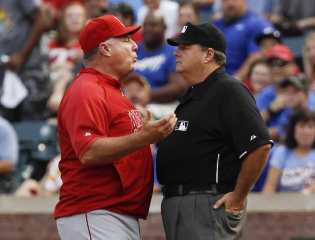 Los Angeles Angels manager Mike Scioscia, left, argues with umpire Jerry Layne, right, after getting ejected from the baseball game against the Texas Rangers during the second inning, Tuesday, July 30, 2013, in Arlington, Texas. (AP Photo/Jim Cowsert)
