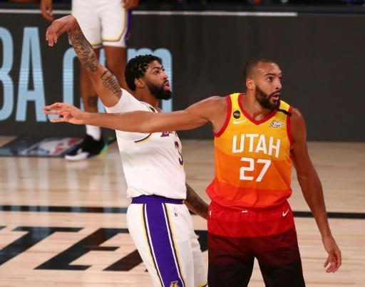 Los Angeles Lakers star Anthony Davis makes a three-pointer despite close attention from Utah's Rudy Gobert in a 116-108 win on Monday