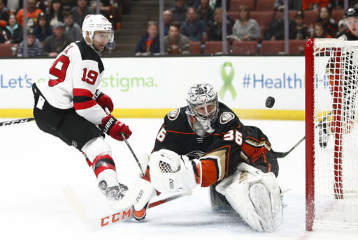 Anaheim Ducks goaltender John Gibson, right, deflects the puck hit by New Jersey Devils' Travis Zajac during the first period of an NHL hockey game Sunday, March 18, 2018, in Anaheim, Calif. (AP Photo/Jae C. Hong)