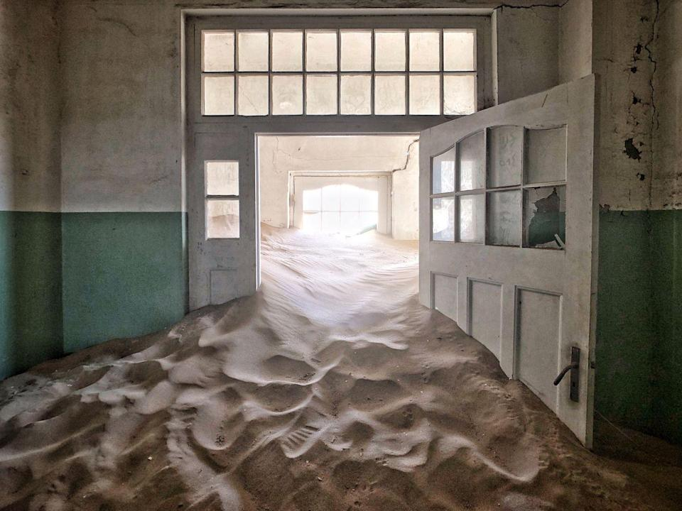 <p>Sand fills the corridor of this abandoned hospital in a ghost town in Africa.</p>