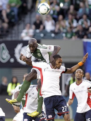 Portland Timbers forward Ryan Johnson, left, heads the ball toward the goal on a corner kick over New England Revolution forward Jerry Bengtson during the first half of an MLS soccer game in Portland, Ore., Thursday, May 2, 2013. (AP Photo/Don Ryan)