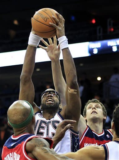 New Jersey Nets' Shelden Williams (33), second from left, grabs the ball in front of Washington Wizards' Jan Vesely, of the Czech Republic, during the second quarter of an NBA basketball game in Newark, N.J., Friday, April 6, 2012. (AP Photo/Mel Evans)
