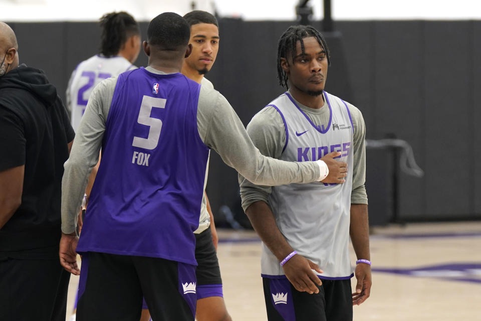Sacramento Kings guard De' Aaron Fox, left, gives teammate, rookie guard Davion Mitchell, right, a pat on the chest during shooting practice during the Kings basketball training camp in Sacramento, Calif., Friday, Oct. 1, 2021. (AP Photo/Rich Pedroncelli)