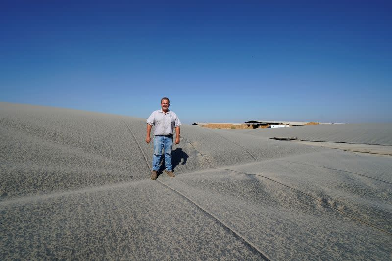 FILE PHOTO: Dairy farmer Joey Airoso stands on top of a methane collecting dome that covers one of his farm's waste collecting ponds in Pixley, California