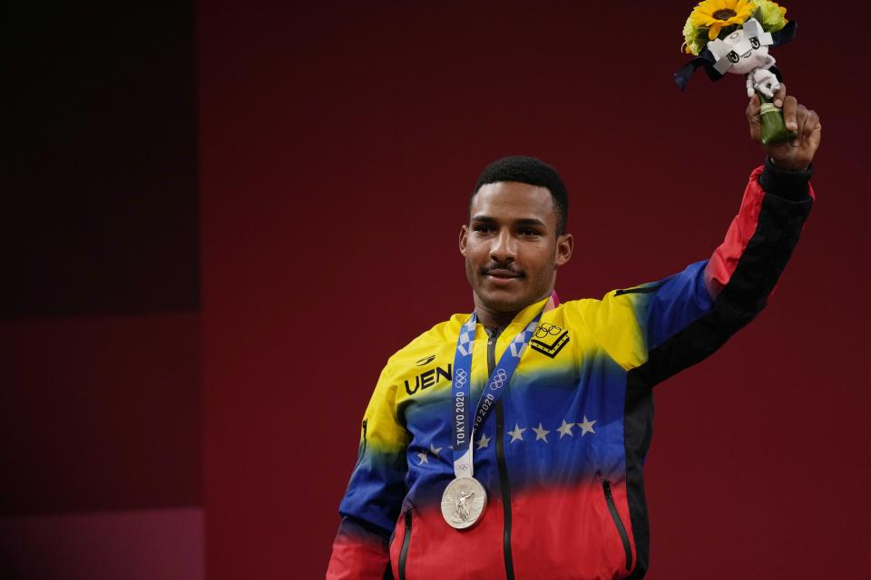 Julio Ruben Mayora Pernia of Venezuela celebrates on the podium after winning the silver medal in the men's 73kg weightlifting event, at the 2020 Summer Olympics, Wednesday, July 28, 2021, in Tokyo, Japan. (AP Photo/Luca Bruno)