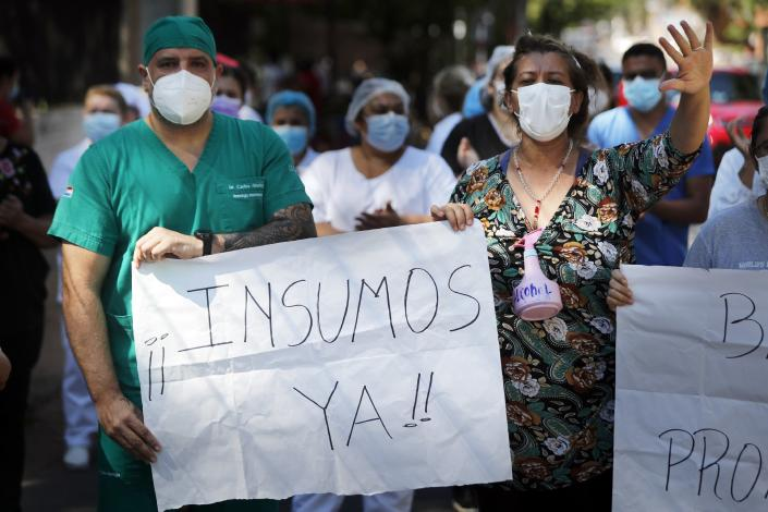 "Respiratory Hospital INERAM health workers and families of patients there protest outside the hospital to demand more materials for the ICU in Asuncion, Paraguay, Wednesday, March 3, 2021, the day after INERAM Director Felipe Gonzalez resigned. The sign in Spanish says: ""Supplies now!"" Without vaccines or basic drugs to combat COVID-19, Paraguay's main public hospitals became unable to receive patients in intensive care units on Wednesday. (AP Photo/Jorge Saenz)"