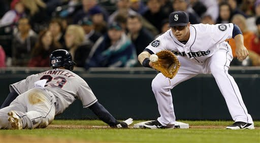 Seattle Mariners first baseman Justin Smoak, right, waits for the ball on a pick-off attempt on Cleveland Indians' Michael Brantley in the first inning of a baseball game Tuesday, April 17, 2012, in Seattle. Brantley was safe. (AP Photo/Elaine Thompson)