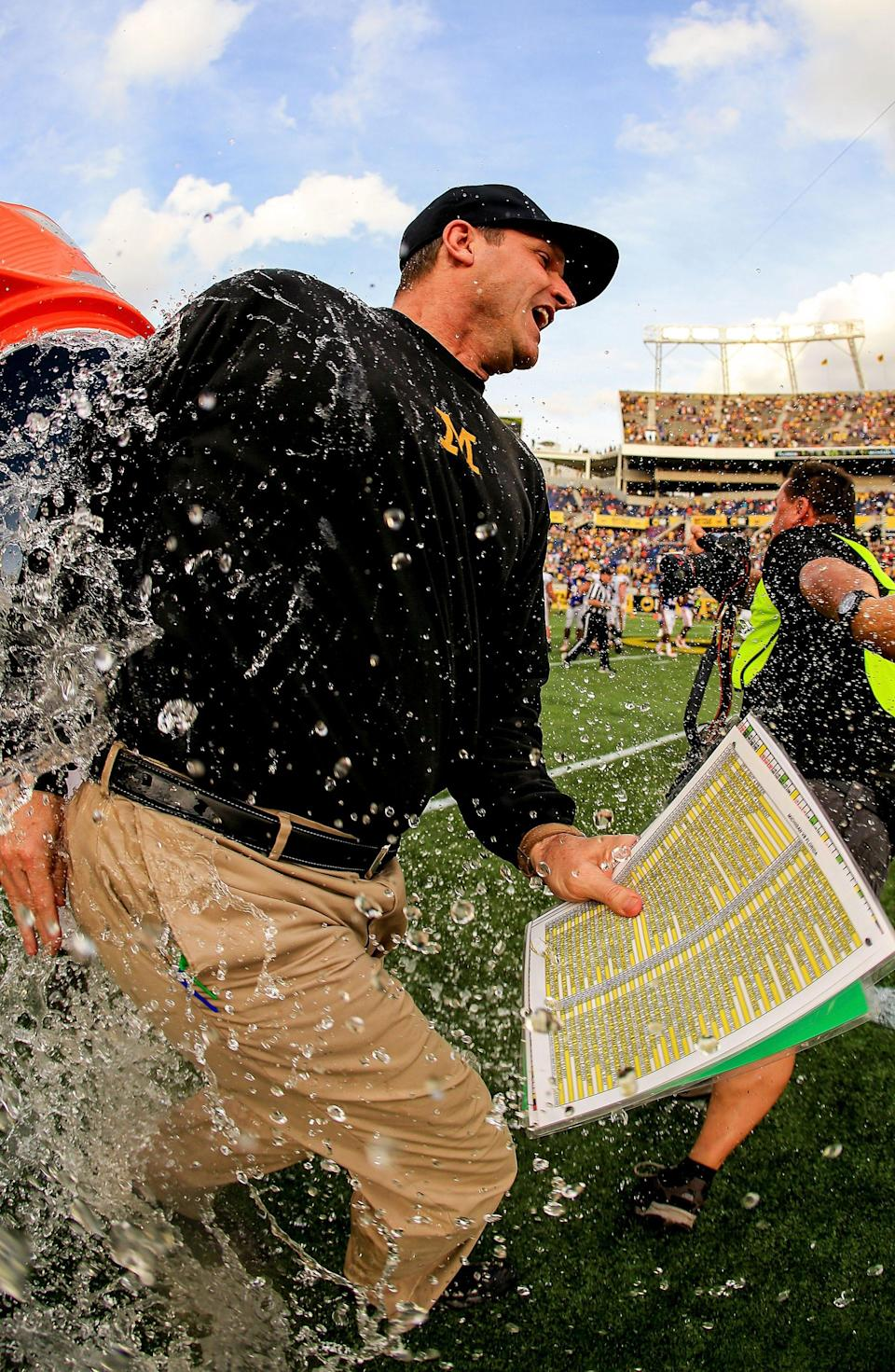 Michigan football coach Jim Harbaugh is dumped with water after the 41-7 win over Florida in the Buffalo Wild Wings Citrus Bowl on Jan. 1, 2016, in Orlando.