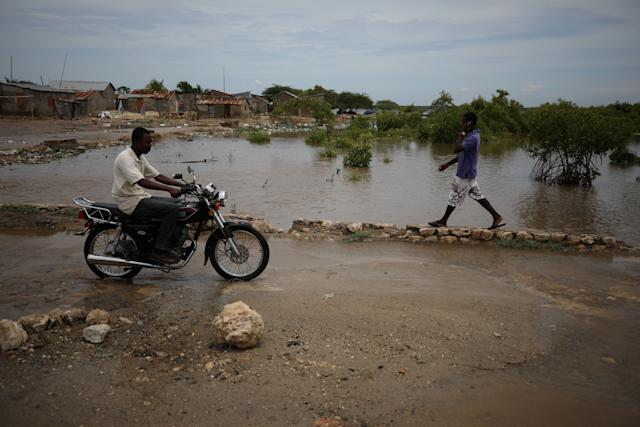 People pass next to a flooded area in Fort Liberte, Haiti