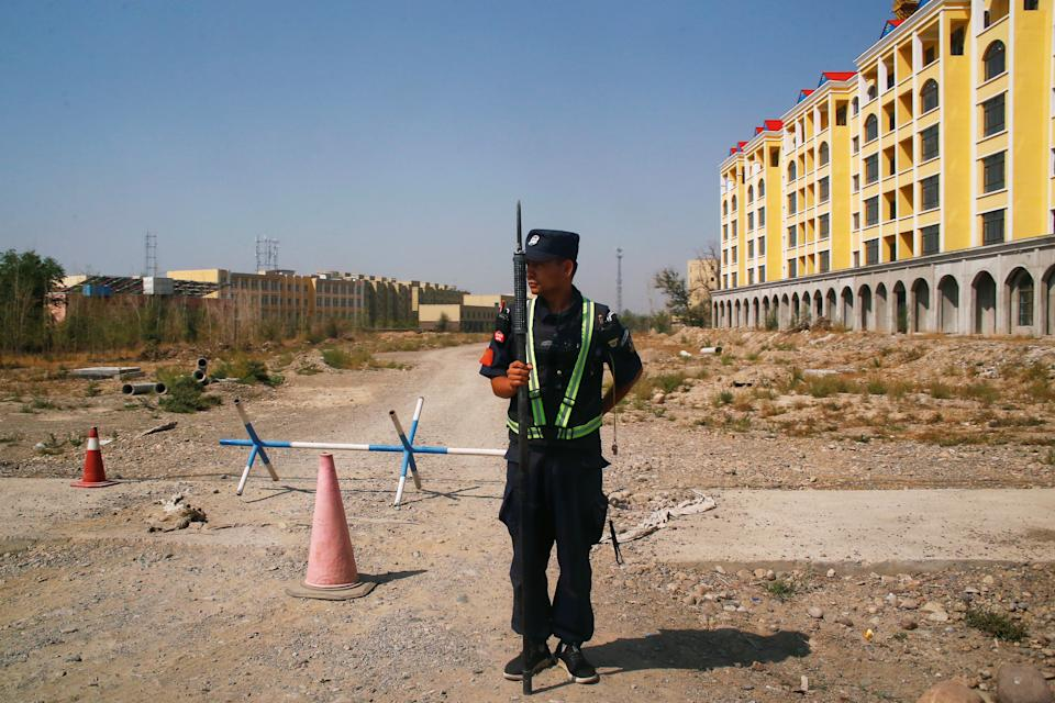 A Chinese police officer takes his position by the road near what is officially called a vocational education centre in Yining in Xinjiang Uighur Autonomous Region, China September 4, 2018. Picture taken September 4, 2018. To match Special Report MUSLIMS-CAMPS/CHINA REUTERS/Thomas Peter