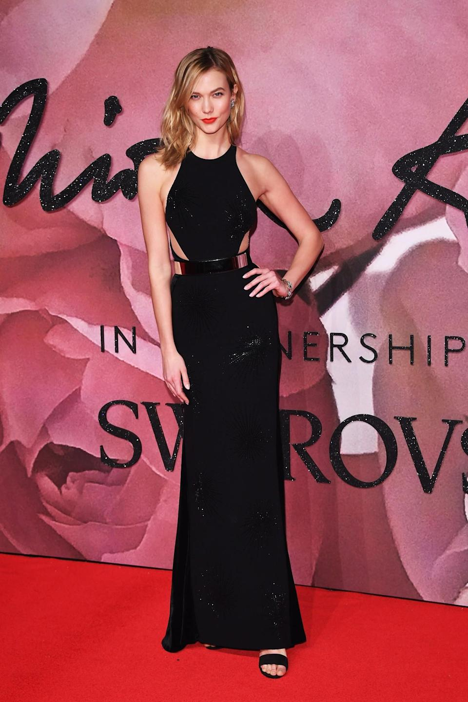 <p>The 24-year-old model chose a sparkly black gown with cutouts. She styled her hair in loose waves and added some color with a bold red lip. (Photo: Getty Images) </p>
