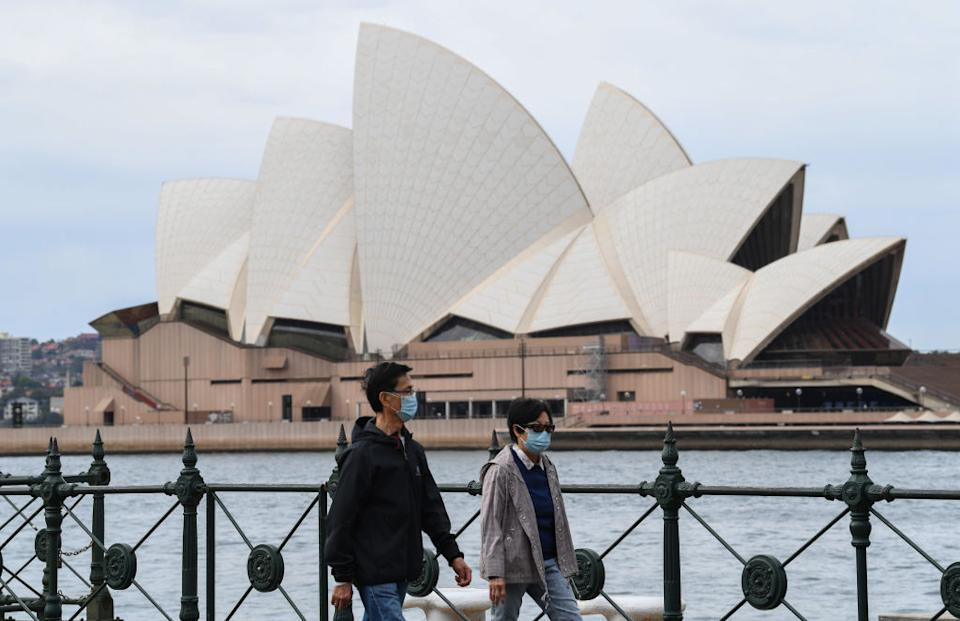 A couple wearing face masks walk with the Opera House in the background in Sydney, Australia.