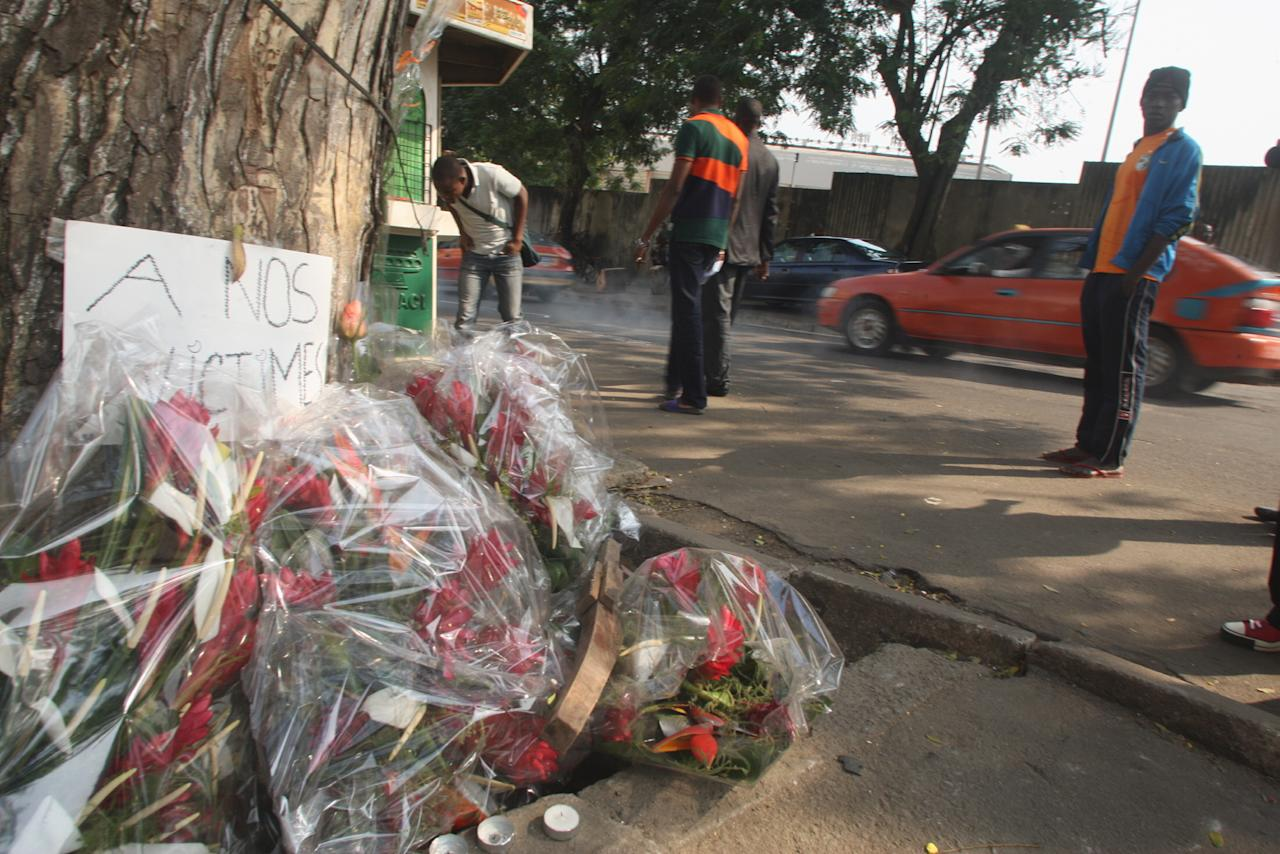 "Flowers are left by a sign reading ""to our victims"" in Abidjan, Ivory Coast, Wednesday Jan. 2, 2013. Survivors of a stampede in Ivory Coast that killed 61 people, most of them children and teenagers, after a New Year's Eve fireworks display at a stadium said Wednesday that barricades stopped them from moving along a main boulevard, causing the crush of people. Ivory Coast President Alassane Ouattara ordered three days of national mourning and launched an investigation into to the causes of the tragedy but two survivors, in interviews with The Associated Press, indicated why so many died in what would normally be an open area, the Boulevard de la Republic. An estimated 50,000 people had gathered in Abidjan's Plateau district to watch the fireworks.(AP Photo/Emanuel Ekra)"