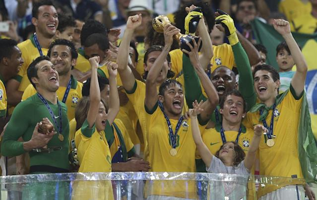 FILE - In this June 30, 2013 file photo, Brazil's Neymar lifts the trophy after the soccer Confederations Cup final against Spain at the Maracana stadium in Rio de Janeiro, Brazil. Brazil won 3-0. (AP Photo/Andre Penner, File)