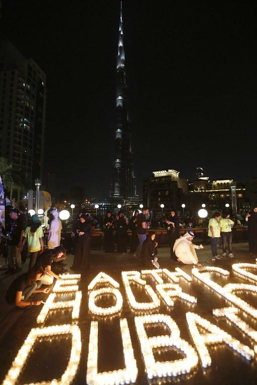"Candles are lit as the lights on the Burj Khalifa tower are switched off for an hour in Downtown Dubai, on March 23, 2013, as iconic landmarks and skylines are plunged into darkness as the ""Earth Hour"" switch-off of lights around the world got under way to raise awareness of climate change. AFP PHOTO/KARIM SAHIB"