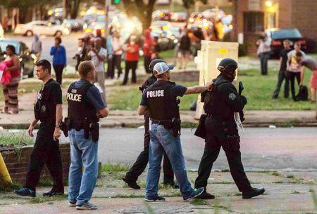 Police monitor the crowd as protesters gathered after a shooting incident in St. Louis, Missouri August 19, 2015.  REUTERS/Kenny Bahr