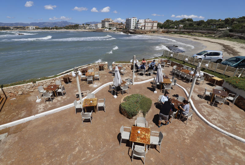 "11 May 2020, Spain, Palma: People sit on the terrace of the bar El Pe-on by the sea. From Monday, in ""Phase 1"" of the relaxation of the corona measures, bars, restaurants, shops, libraries and religious places of worship, among others, will be allowed to reopen. Photo: Clara Margais/dpa (Photo by Clara Margais/picture alliance via Getty Images)"