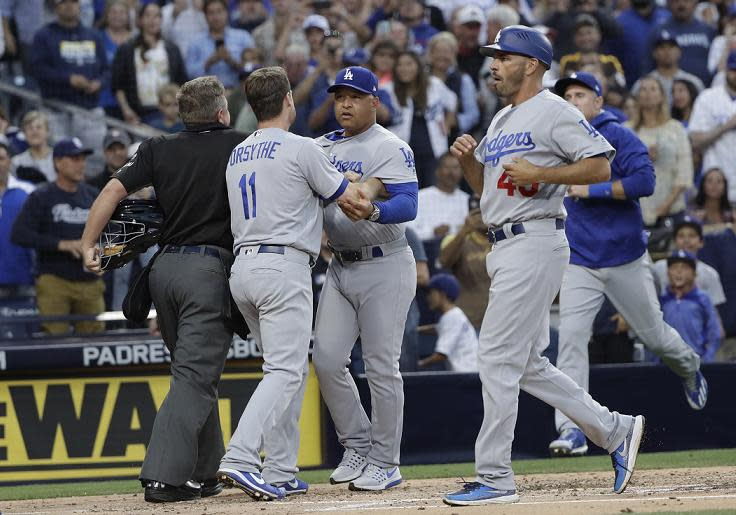 Los Angeles Dodgers manager Dave Roberts (center) is held back after getting into a heated confrontation with Padres manager Andy Green. (AP)