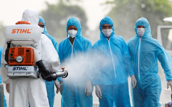 A health worker in a white protective suit sprays disinfectant at Vietnamese construction workers infected with the coronavirus disease (COVID-19), upon their arrival at the tropical diseases hospital after being repatriated from Equatorial Guinea via a specially-adapted Vietnam Airlines plane filled with medical equipment and negative pressure chambers, in Hanoi, Vietnam July 29, 2020. REUTERS/Kham - Reuters