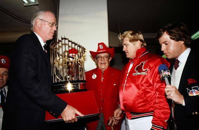 MLB Commissioner Bowie Kuhn presents the World Series trophy to Gussie Busch and Whitey Herzog of the St. Louis Cardinals. (Photo by Rich Pilling/Getty Images)