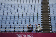 Volunteers wave prior to a women's soccer match between China and Brazil at the 2020 Summer Olympics, Wednesday, July 21, 2021, in Rifu, Japan. (AP Photo/Andre Penner)