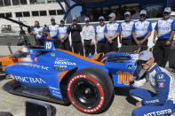 Driver Alex Palou, front right, poses by his car and team after winning the first pole of his career during qualifying for Sunday's IndyCar auto race, Saturday, Sept. 11, 2021, at Portland International Raceway in Portland, Ore. (AP Photo/Jenna Fryer)