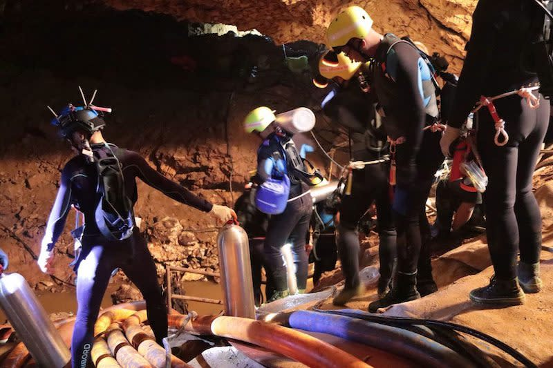 <p>The Royal Thai Navy released this image on July 7, 2018, showing rescue team members walking inside the cave with oxygen tanks where the boys and their coach were trapped for weeks. Photo from the Royal Thai Navy via The Associated Press. </p>
