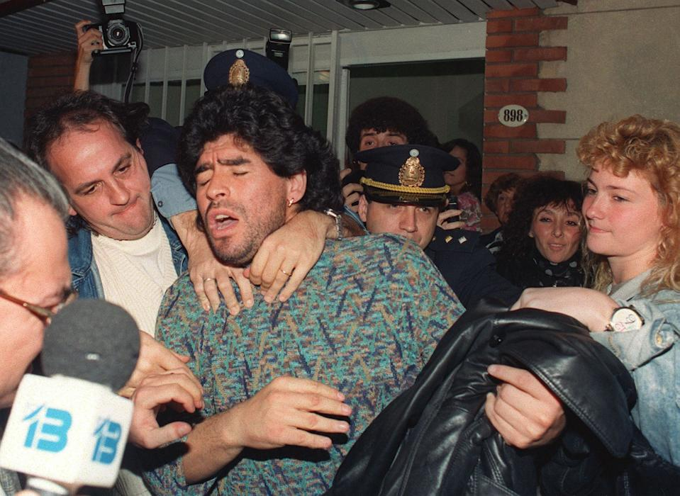 Diego Maradona is taken away by police from a Buenos Aires apartment, after being arrested for possession of half-kilo of cocaine. (PHOTO: Daniel Luna/AFP via Getty Images)