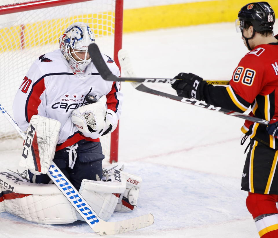Washington Capitals goaltender Braden Holtby (70) makes a save as Calgary Flames left wing Andrew Mangiapane (88) watches during the third period of an NHL hockey game Tuesday, Oct. 22, 2019, in Calgary, Alberta. (Larry MacDougal/The Canadian Press via AP)