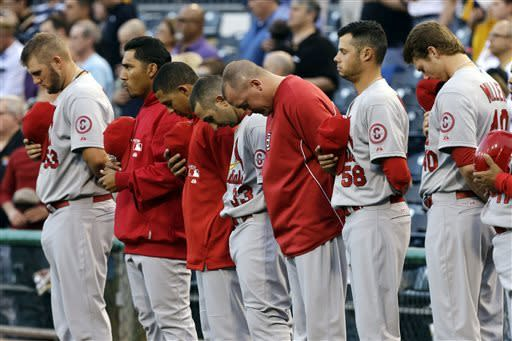 Members of the St. Louis Cardinals observe a moment of silence for the victims of the bombings at the Boston Marathon before a baseball game against the Pittsburgh Pirates in Pittsburgh, Tuesday, April 16, 2013. (AP Photo/Gene J. Puskar)
