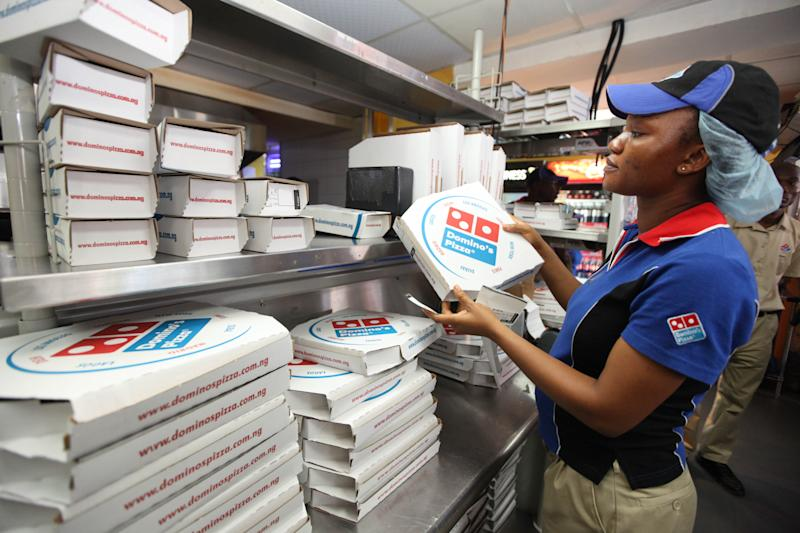 In this photo taken Sunday, Feb. 10, 2013 a worker prepares boxes at a Domino's pizza restaurant in Lagos, Nigeria. As Nigeria's middle class grows along with the appetite for foreign brands in Africa's most populous nation, more foreign restaurants and lifestyle companies are entering the country. And the draw on Nigerians' new discretionary spending has also put new expectations on providing quality service in a nation where many have grown accustomed to expecting very little. ( AP Photo/Sunday Alamba)