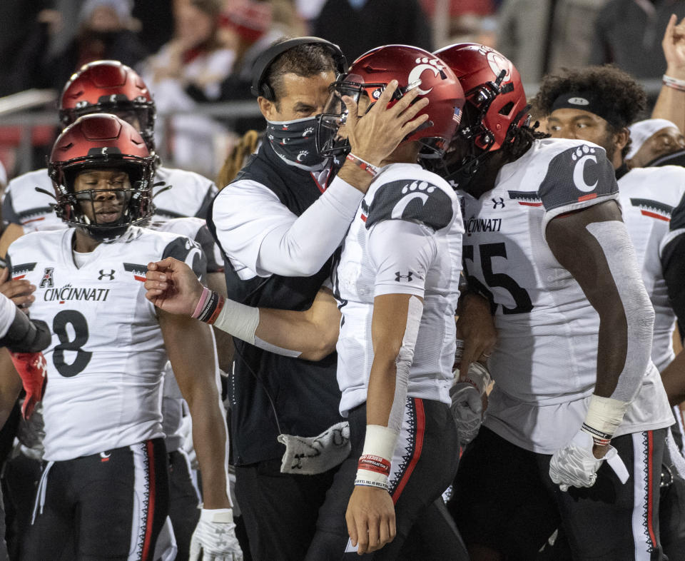 Cincinnati head coach Luke Fickell congratulates quarterback Desmond Ridder after Ridder rushed for his third touchdown of the game during the second half of an NCAA college football game against SMU Saturday, Oct. 24, 2020, in Dallas. Cincinnati won 42-13 and Ridder finished with 179 yards rushing. (AP Photo/Jeffrey McWhorter)