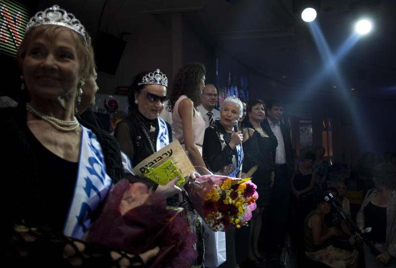 "Hava Hershkovitz, third from right, a Holocaust survivor and winner of a beauty pageant, speaks to the crowd in the northern Israeli city of Haifa, Thursday, June 28, 2012. Fourteen women who lived through the horrors of World War II paraded on stage Thursday night in an unusual pageant, vying for the honor of being Israel's first ""Miss Holocaust Survivor."" (AP Photo/Sebastian Scheiner)"