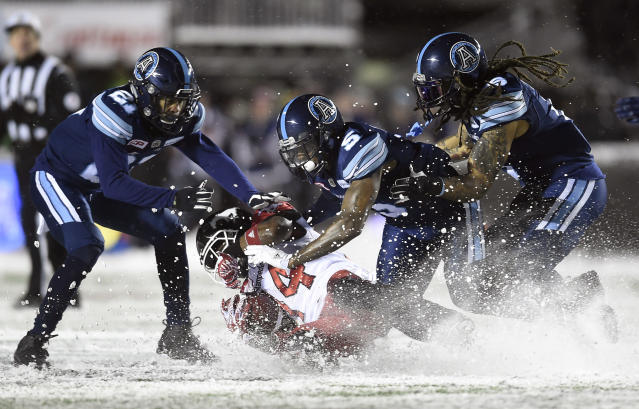 Toronto Argonauts defensive back Jermaine Gabriel (5), linebacker Marcus Ball (6) and defensive back Qudarius Ford (21) tackle Calgary Stampeders running back Roy Finch (14) in the snow during second-half CFL football game action in the Grey Cup, Sunday, Nov. 26, 2017, in Ottawa. (Nathan Denette/The Canadian Press via AP)