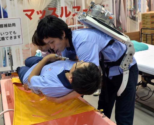 A Japanese elderly care company Asahi Sun Clean employee (top) wearing a power suit, called 'Muscle Suit,' lifts a fellow worker during a demonstration at the annual Internatinal Robot Exhibition in Tokyo, on November 6, 2013