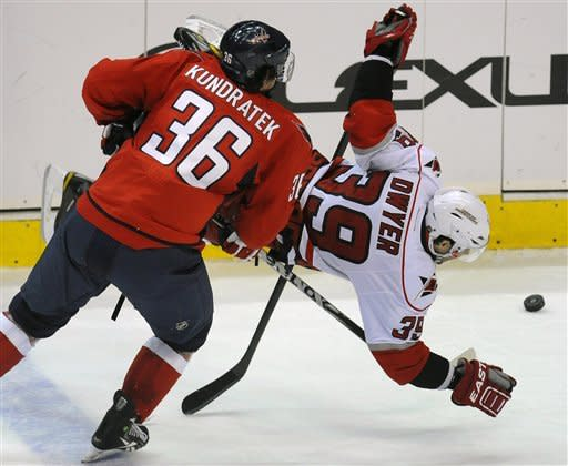 Carolina Hurricanes' Patrick Dwyer (39) is tripped by Washington Capitals' Tomas Kundratek (36), of the Czech Republic, during the third period of their NHL hockey game, Sunday, Jan. 15, 2012, in Washington. Kundratek received a penalty on the play. The Capitals defeated the Hurricanes 2-1. (AP Photo/Richard Lipski)