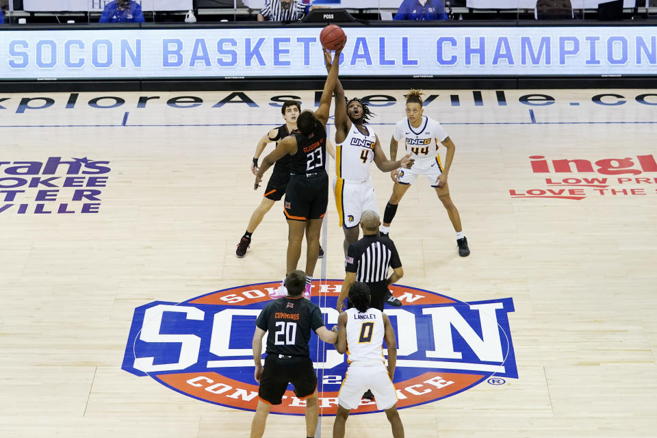Mercer forward James Glisson III (23) and UNC-Greensboro forward Mohammed Abdulsalam (4) tip off for the start of an NCAA men's college basketball championship game for the Southern Conference tournament, Monday, March 8, 2021, in Asheville, N.C. (AP Photo/Kathy Kmonicek)