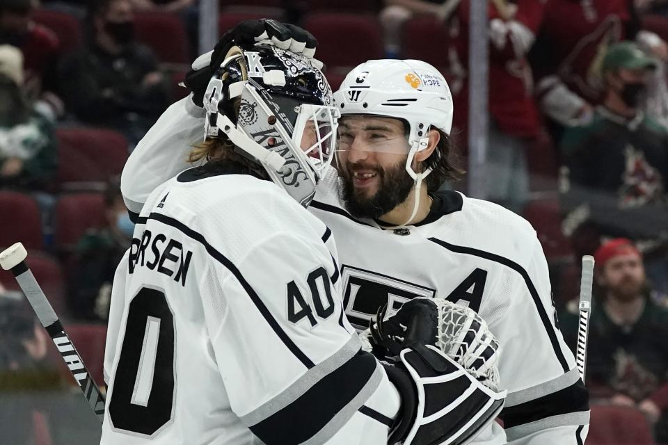 Los Angeles Kings goaltender Calvin Petersen (40) and defenseman Drew Doughty, right, congratulate each other at the end of the team's NHL hockey game against the Arizona Coyotes on Wednesday, May 5, 2021, in Glendale, Ariz. The Kings won 4-2. (AP Photo/Ross D. Franklin)